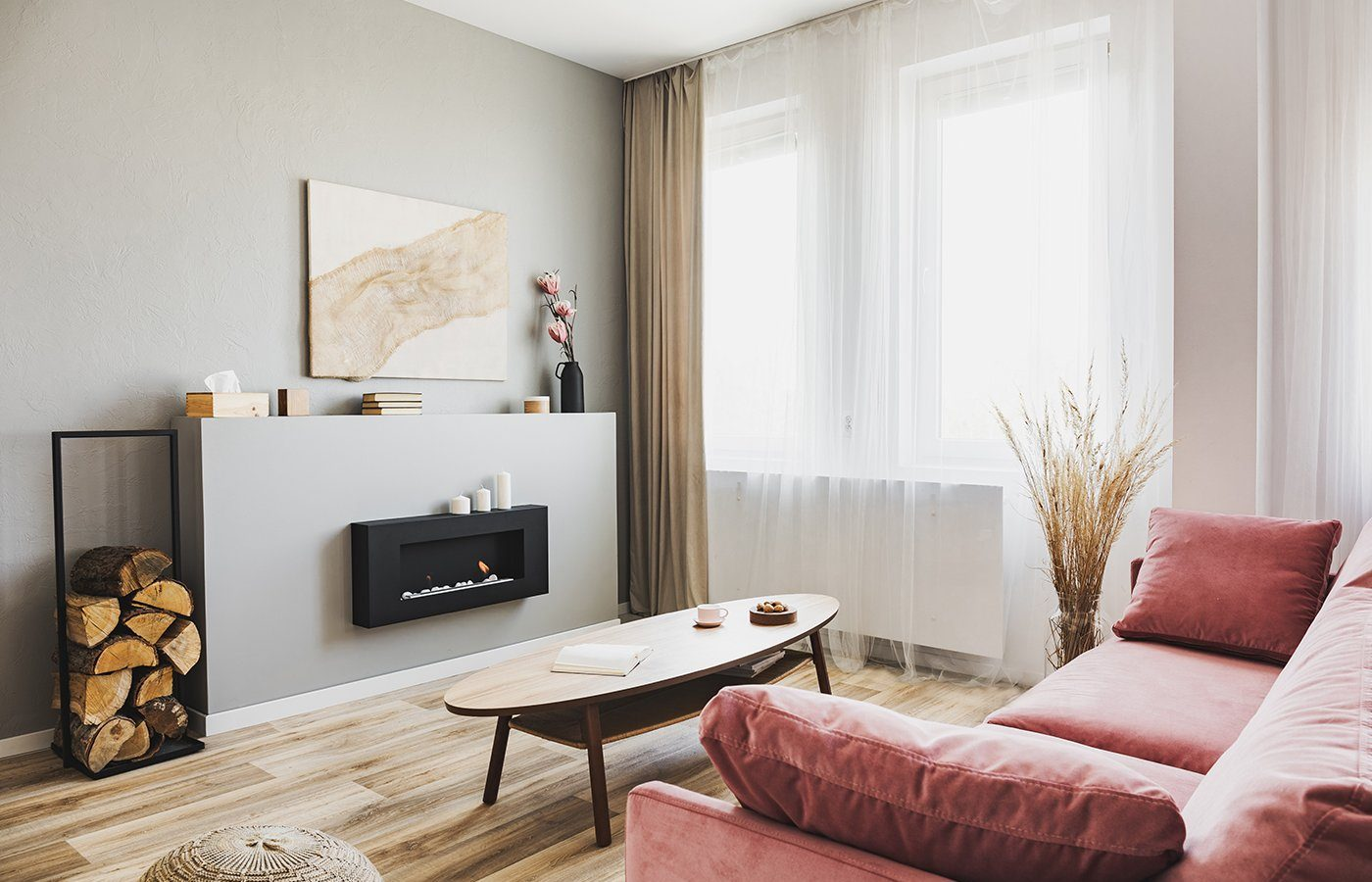 Stylish living room interior with pastel pink sofa, wooden coffe